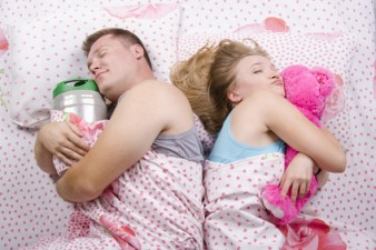 Пара спит в постели: муж с бочонком, жена с мишкой