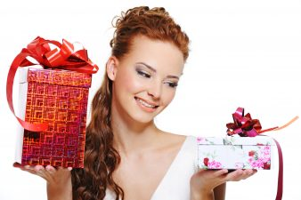 Happy smiling girl choosing between two gifts