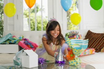 Excited Girl Unwrapping Gifts at Birthday Party