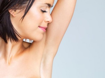 Close up of beautiful brunette woman with arm up smelling armpit-Copyspace
